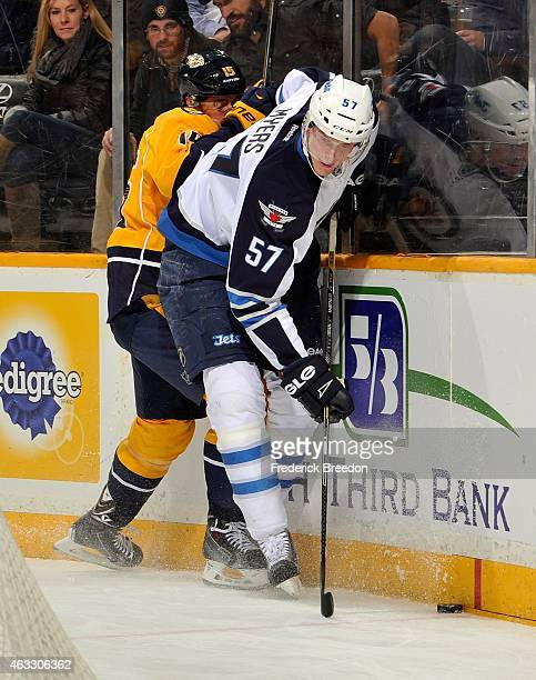 Tyler Myers of the Winnipeg Jets fights for the puck against Craig Smith of the Nashville Predators during the first period of a game at Bridgestone...