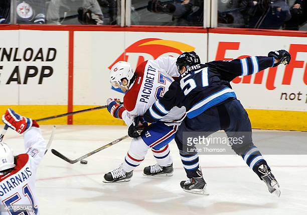 Tyler Myers of the Winnipeg Jets knocks the puck away from Max Pacioretty of the Montreal Canadiens during second period action on March 26 2015 at...