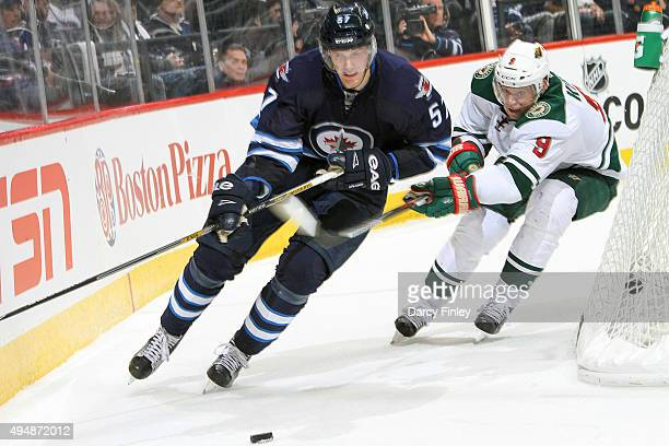 Tyler Myers of the Winnipeg Jets plays the puck around the net away from Mikko Koivu of the Minnesota Wild during third period action at the MTS...