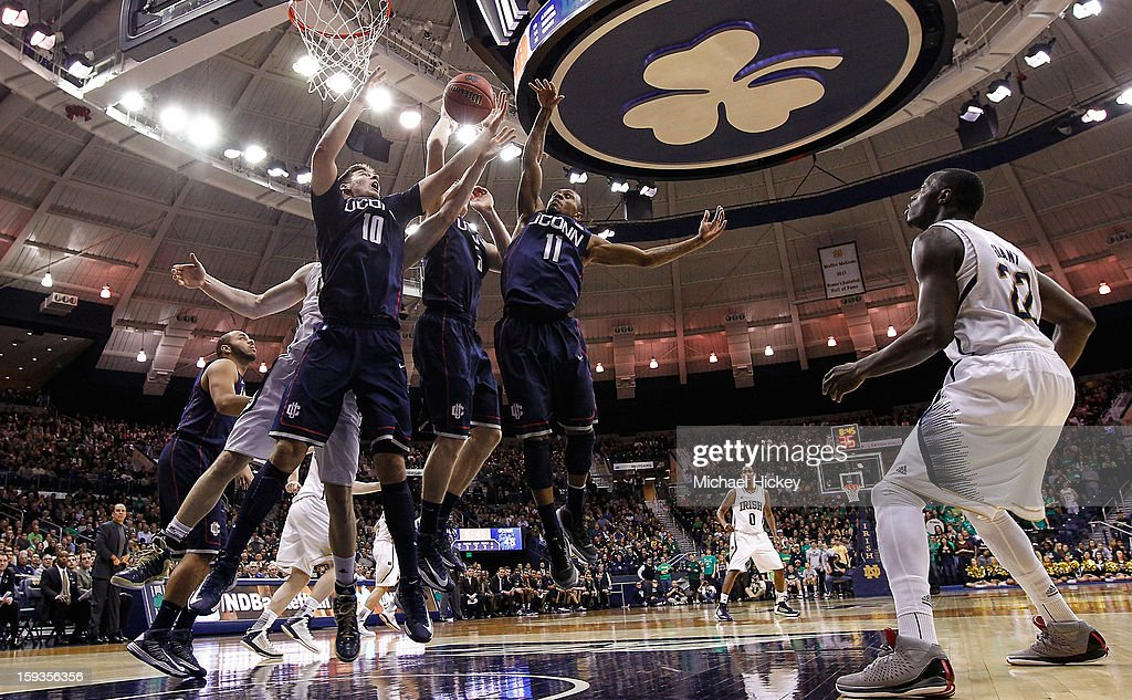 Tyler Olander #10, Niels Giffey #5 and Ryan Boatright #11 of the Connecticut Huskies reach for a rebound against the Notre Dame Fighting Irish at Purcel Pavilion on January 12, 2013 in South Bend, Indiana. Connecticut defeated Notre Dame 65-58.