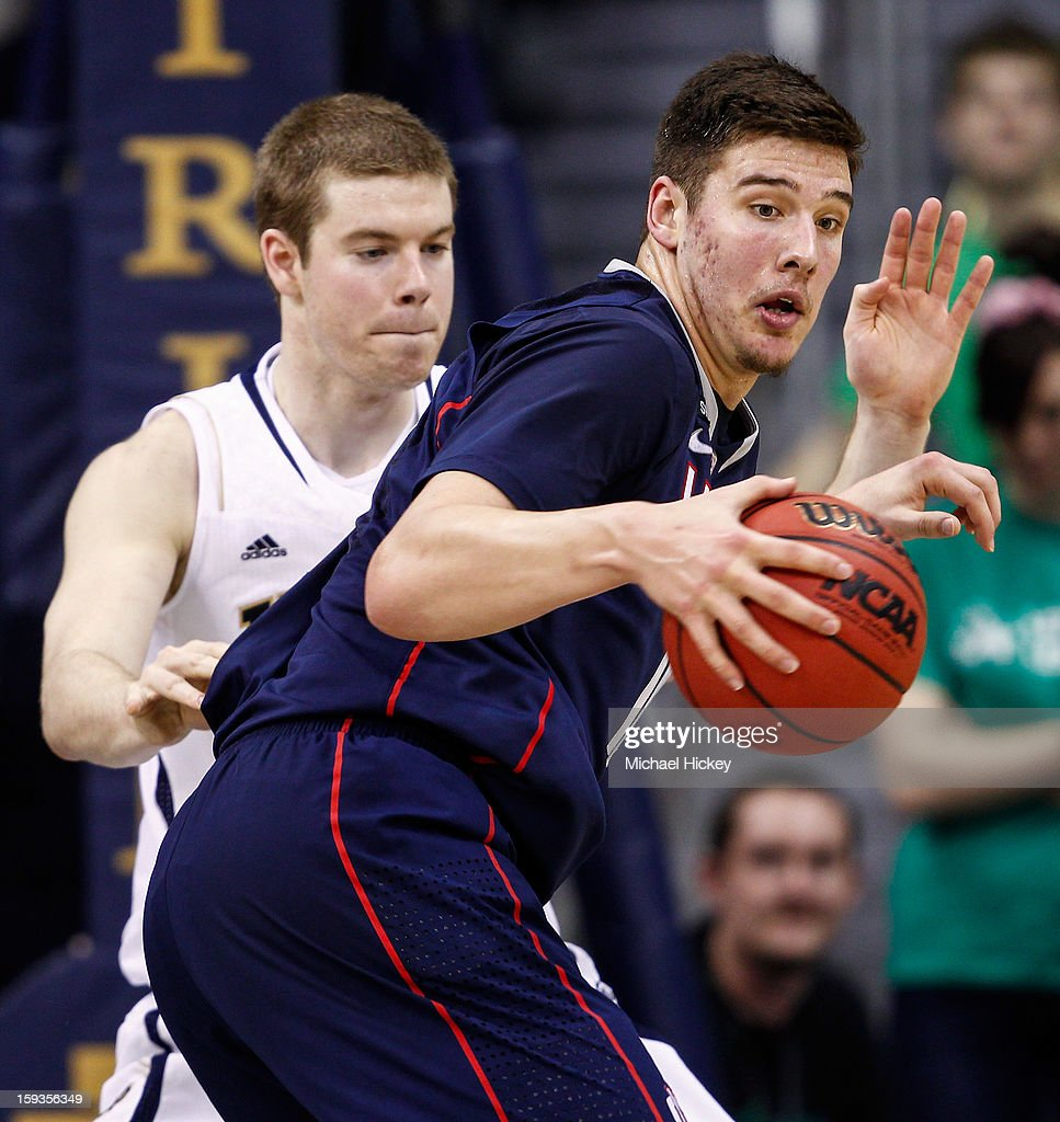 Tyler Olander #10 of the Connecticut Huskies dribbles the ball against <a gi-track='captionPersonalityLinkClicked' href=/galleries/search?phrase=Scott+Martin+-+Basketballspieler&family=editorial&specificpeople=15168896 ng-click='$event.stopPropagation()'>Scott Martin</a> #14 of the Notre Dame Fighting Irish at Purcel Pavilion on January 12, 2013 in South Bend, Indiana. Connecticut defeated Notre Dame 65-58.