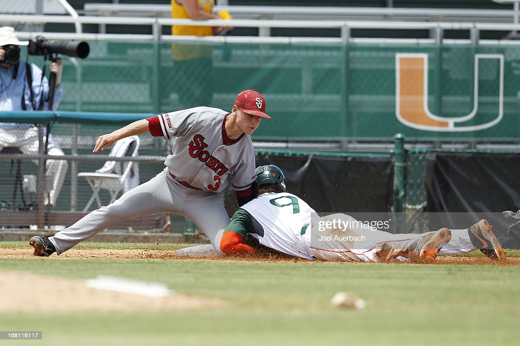 Tyler Palmer #9 of the Miami Hurricanes is tagged out at third base by Sean O'Hare #3 of the St John's Red Storm in the bottom of the third inning on May 5, 2013 at Alex Rodriguez Park at Mark Light Field in Coral Gables, Florida. Miami defeated St John's 6-4 and swept the weekend series.