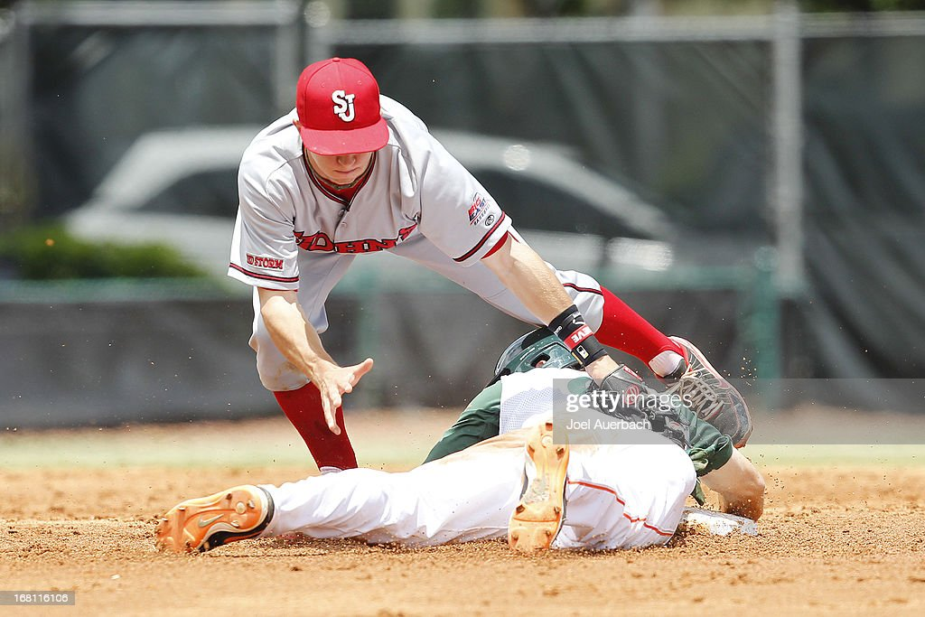 Tyler Palmer #9 of the Miami Hurricanes steals second base under the tag by Ty Blankmeyer #0 of the St John's Red Storm on May 5, 2013 at Alex Rodriguez Park at Mark Light Field in Coral Gables, Florida. Miami defeated St John's 6-4 and swept the weekend series.