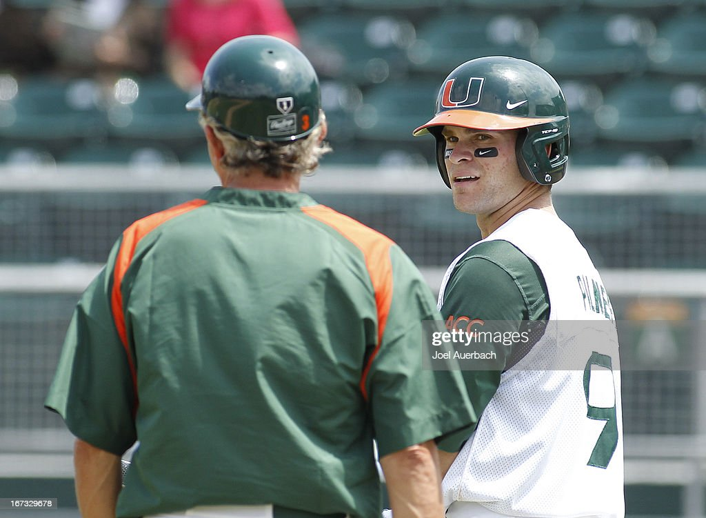 Tyler Palmer #9 talks to head coach Jim Morris #3 of the Miami Hurricanes during a break in action against the Clemson Tigers on April 21, 2013 at Alex Rodriguez Park at Mark Light Field in Coral Gables, Florida. Miami defeated Clemson 7-0.