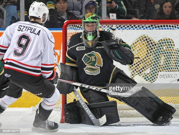 Tyler Parsons of the London Knights grabs a puck against Ethan Szypula of the Owen Sound Attack during an OHL game at Budweiser Gardens on February 3...