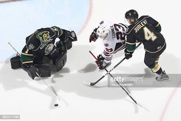 Tyler Parsons of the London Knights looks to cover a puck before Johnny Corneil of the Niagara IceDogs can get to it during an OHL game at Budweiser...