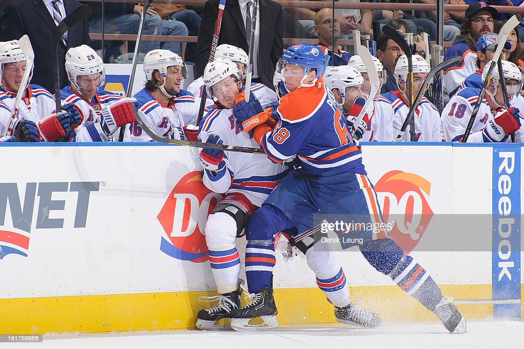 Tyler Pitlick #68 of the Edmonton Oilers shoves Danny Kristo #46 of the New York Rangers during a preseason NHL game at Rexall Place on September 24, 2013 in Edmonton, Alberta, Canada.