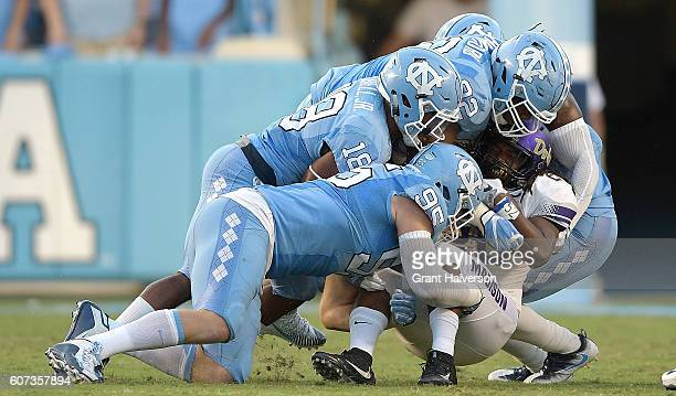 Tyler Powell Corey Bell Jr #18 and Aaron Crawford of the North Carolina Tar Heels tackle Cardon Johnson of the James Madison Dukes during the game at...