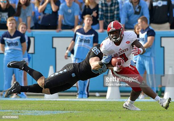 Tyler Powell of the North Carolina Tar Heels tackles Reggie Gallaspy II of the North Carolina State Wolfpack during their game at Kenan Stadium on...