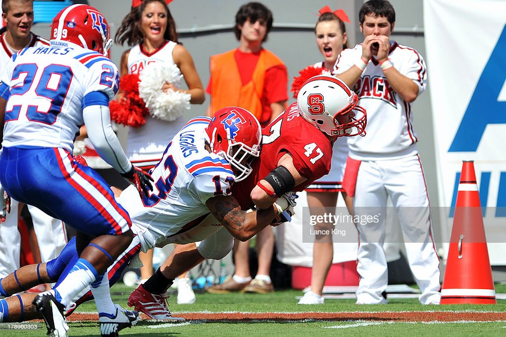 Tyler Purvis #47 of the North Carolina State Wolfpack fights for extra yardage against Le'Vander Liggins #13 of the Louisiana Tech Bulldogs at Carter-Finley Stadium on August 31, 2013 in Raleigh, North Carolina.
