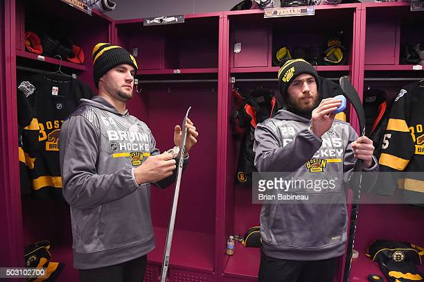 Tyler Randell and Landon Ferraro of the Boston Bruins work on their sticks in the locker room prior to the 2016 Bridgestone NHL Classic against the...