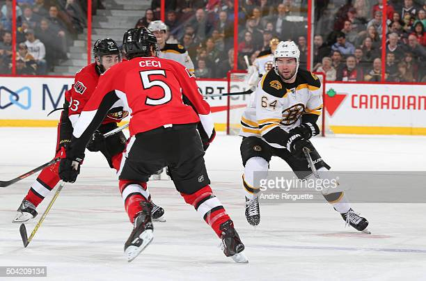 Tyler Randell of the Boston Bruins chips the puck into the offensive zone against Cody Ceci of the Ottawa Senators at Canadian Tire Centre on January...