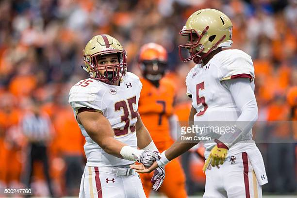 Tyler Rouse of the Boston College Eagles and Jeff Smith slap hands during the game against the Syracuse Orange on November 28 2015 at The Carrier...