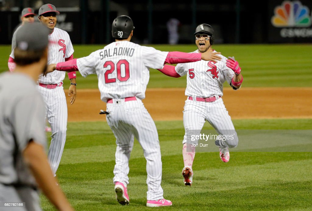 Tyler Saladino #20 of the Chicago White Sox celebrates after scoring on a walk off RBI single by Yolmer Sanchez #5 at Guaranteed Rate Field on May 13, 2017 in Chicago, Illinois. Players and umpires are wearing pink to celebrate Mother's Day weekend and support breast cancer awareness. The White Sox won 5-4.