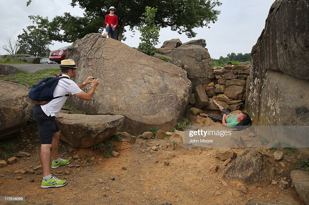 Tyler Schmidt, 16, from Austin, Texas poses for a picture while re-enacting the famous 'The Home of a Rebel Sharpshooter' photo on July 2, 2013 in Gettysburg, Pennsylvania, the 150th anniversary of the Battle of Gettysburg. Some of the public visiting the historic site choose to recreate the macabre scene, as part of their battlefield experience. The original photo featured a dead Confederate soldier in a photo taken by Alexander Gardner on July 5, 1863. The photograph was later discovered to be staged, the body of the 'sharpshooter' having been brought from another place on the battlefield for the photograph and the gun not a sharp's rifle.