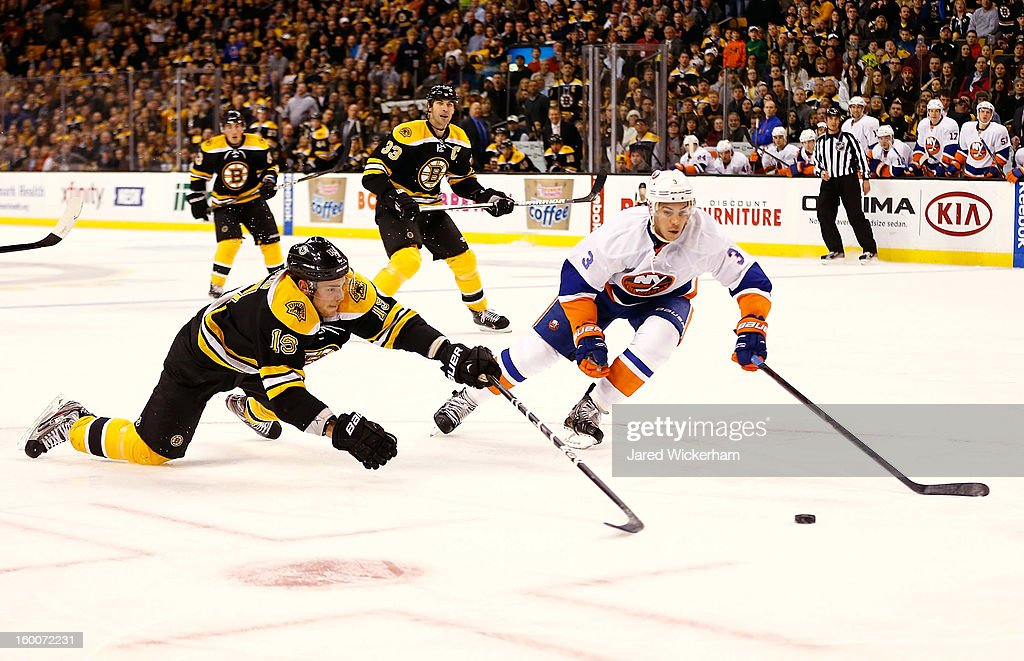 Tyler Seguin #19 of the Boston Bruins dives for a loose puck in front of Travis Hamonic #3 of the New York Islanders during the game on January 25, 2013 at TD Garden in Boston, Massachusetts.