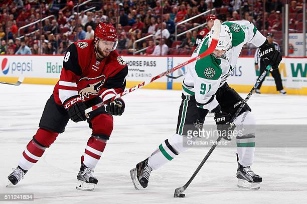 Tyler Seguin of the Dallas Stars skates with the puck ahead of Tobias Rieder of the Arizona Coyotes during the first period of the NHL game at Gila...