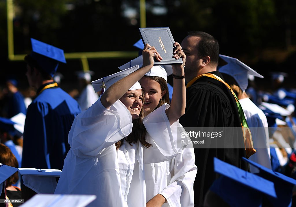 Tyler Smith, 18, holds up her diploma during Cherry Creek High School graduation at Stutler Bowl, May 25, 2016. This is the school's sixty-first annual commencement.