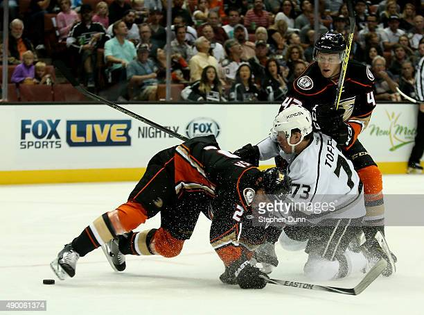 Tyler Toffoli of the Los Angeles Kings collides with Kevin Bieksa and Josh Manson of the Anaheim Ducks as they chase the puck during preseason at...