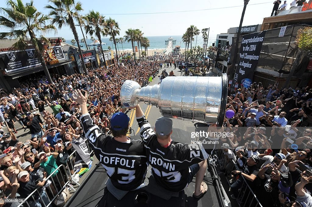 Tyler Toffoli #73 waves to the crowd as Dustin Brown #23 of the Los Angeles Kings hoists the Stanley Cup up in the air during the Los Angeles Kings South Bay Victory Parade on June 18, 2014 in Redondo Beach, California.