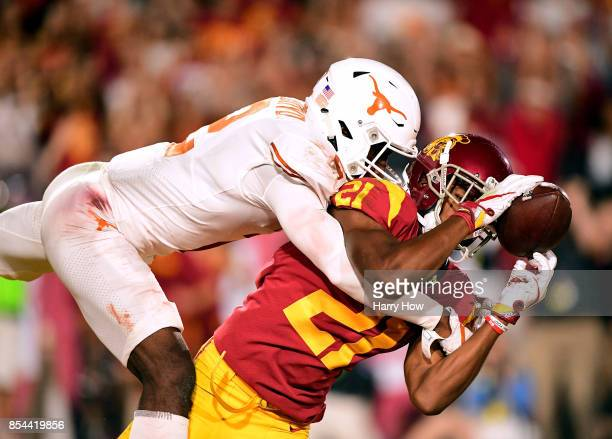 Tyler Vaughns of the USC Trojans loses control of the ball as he is tackled by Kris Boyd of the Texas Longhorns at Los Angeles Memorial Coliseum on...