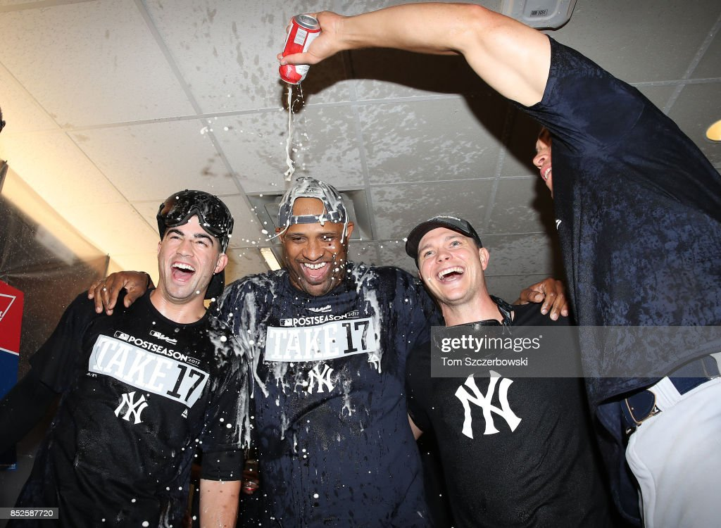 Tyler Wade #39 of the New York Yankees and CC Sabathia #52 and Sonny Gray #55 are sprayed as they celebrate their playoff-clinching victory during MLB game action against the Toronto Blue Jays at Rogers Centre on September 23, 2017 in Toronto, Canada.