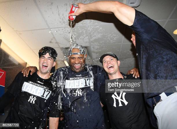 Tyler Wade of the New York Yankees and CC Sabathia and Sonny Gray are sprayed as they celebrate their playoffclinching victory during MLB game action...