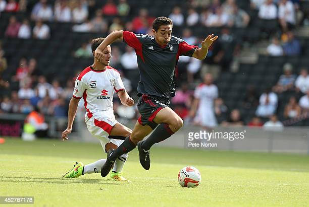 Tyler Walker of Nottingham Forest attempts to move forward with the ball away from George Baldock of MK Dons during the PreSeason Friendly between MK...