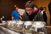 Tyler Williams of Blanchester Ohio selects marijuana strains to purchase at the 3D Denver Discrete Dispensary on January 1 2014 in Denver Colorado...