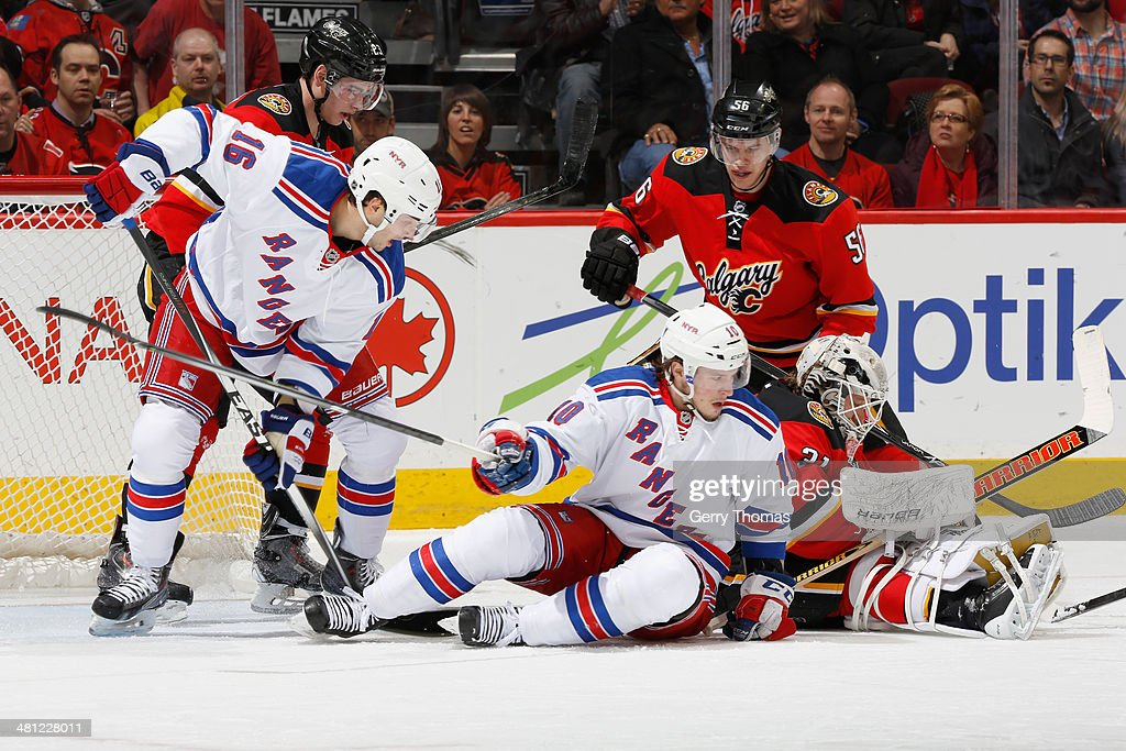 Tyler Wotherspoon #56 and Karri Ramo #31 of the Calgary Flames defend the net against J.T. Miller #10 and Derick Brassard #16 of the New York Rangers at Scotiabank Saddledome on March 28, 2014 in Calgary, Alberta, Canada.