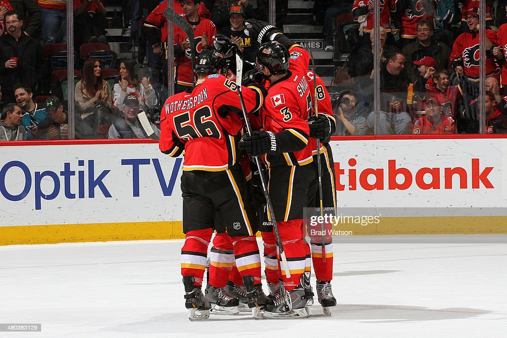 Tyler Wotherspoon #56, Ladislav Smid #3 and Joe Colborne #8 of the Calgary Flames celebrate a goal against the San Jose Sharks at Scotiabank Saddledome on March 24, 2014 in Calgary, Alberta, Canada.
