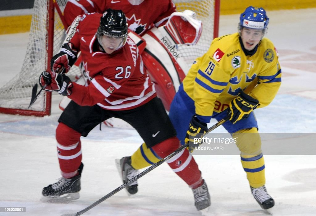 Tyler Wotherspoon (L) of Canada and Sweden's Elias Lindholm in action during the U20 Premiere WC ice hockey match Canada vs Sweden in Helsinki, Finland, December 22, 2012. AFP PHOTO / LEHTIKUVA / Jussi Nukari