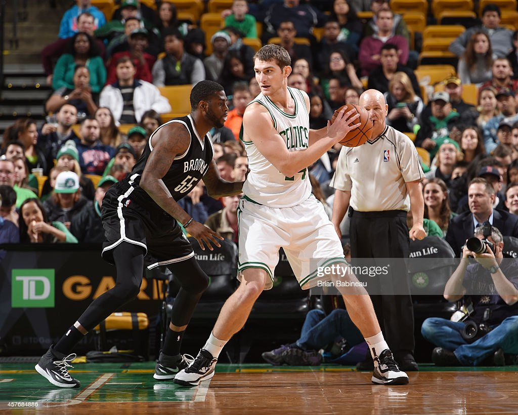 Tyler Zeller of the Boston Celtics defends the ball against Willie Reed of the Brooklyn Nets during the game on October 22 2014 at the TD Garden in...