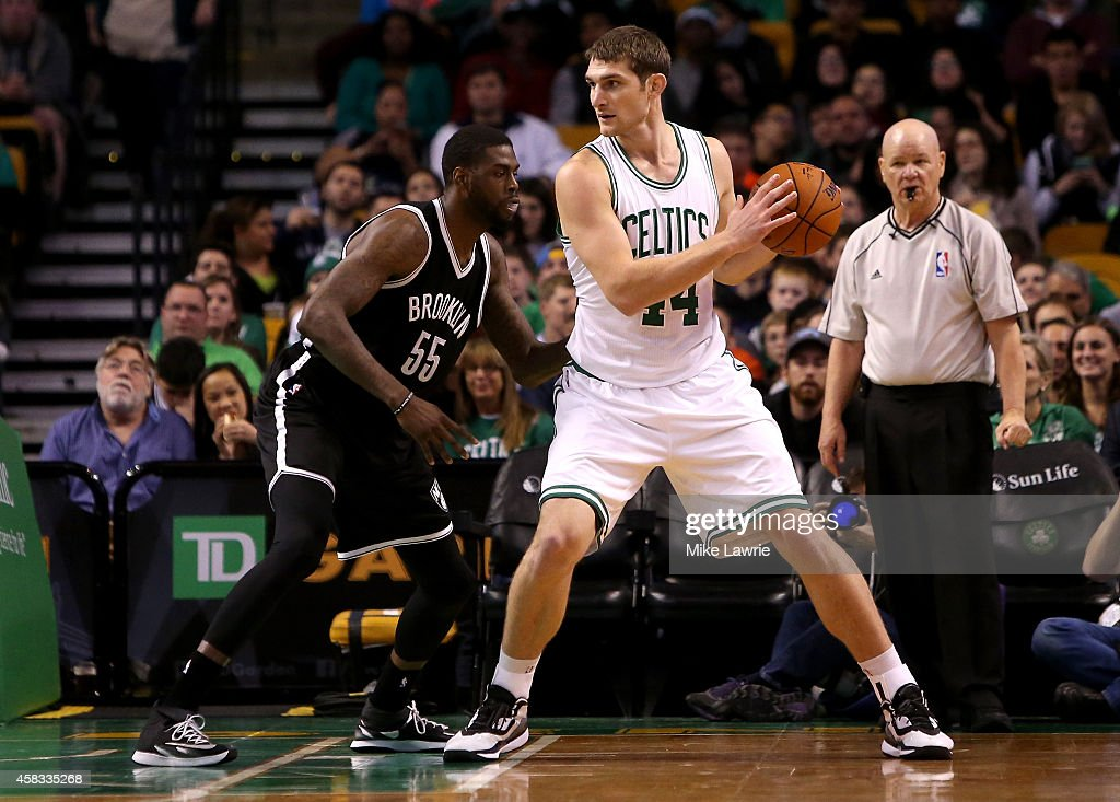 Tyler Zeller of the Boston Celtics handles the ball against Willie Reed of the Brooklyn Nets during a preseason game at TD Garden on October 22 2014...