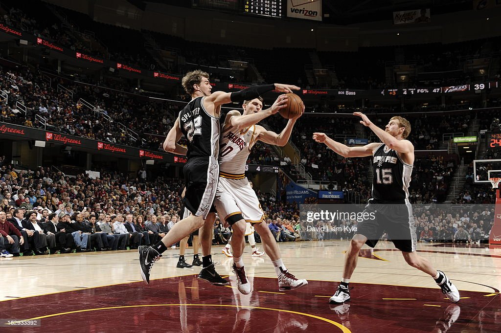 Tyler Zeller #40 of the Cleveland Cavaliers goes to the basket against Tiago Splitter #22 and Matt Bonner #15 of the San Antonio Spurs at The Quicken Loans Arena on February 13, 2013 in Cleveland, Ohio.