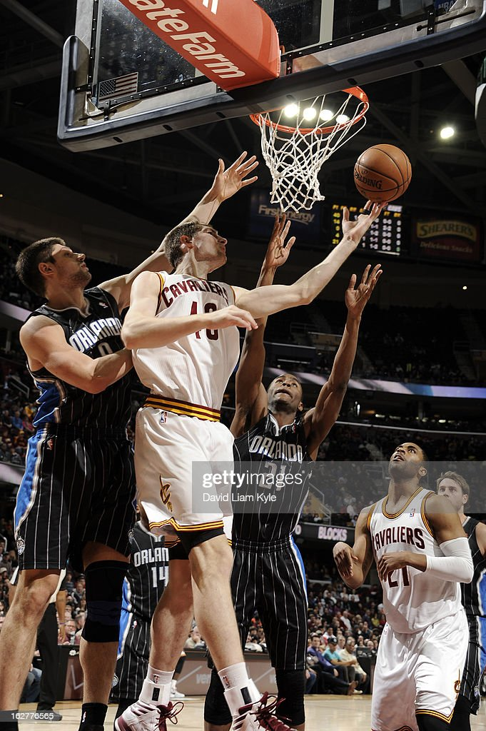 Tyler Zeller #40 of the Cleveland Cavaliers shoots a reverse layup against Nikola Vucevic #9 and Moe Harkless #21 of the Orlando Magic at The Quicken Loans Arena on February 8, 2013 in Cleveland, Ohio.