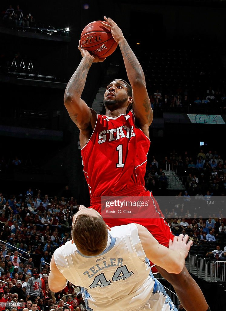 Tyler Zeller of the North Carolina Tar Heels draws a charge from Richard Howell of the North Carolina State Wolfpack during the semifinals of the...