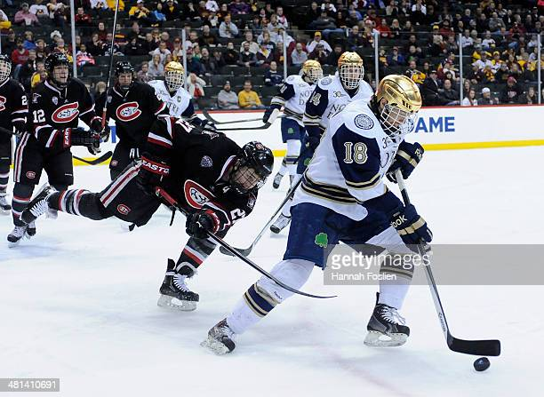 J Tynan of the Notre Dame Fighting Irish controls the puck against Nick Oliver of the St Cloud State Huskies during the second period of the West...