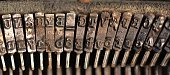 Typebars in an old Royal typewriter, aged and discolored.
