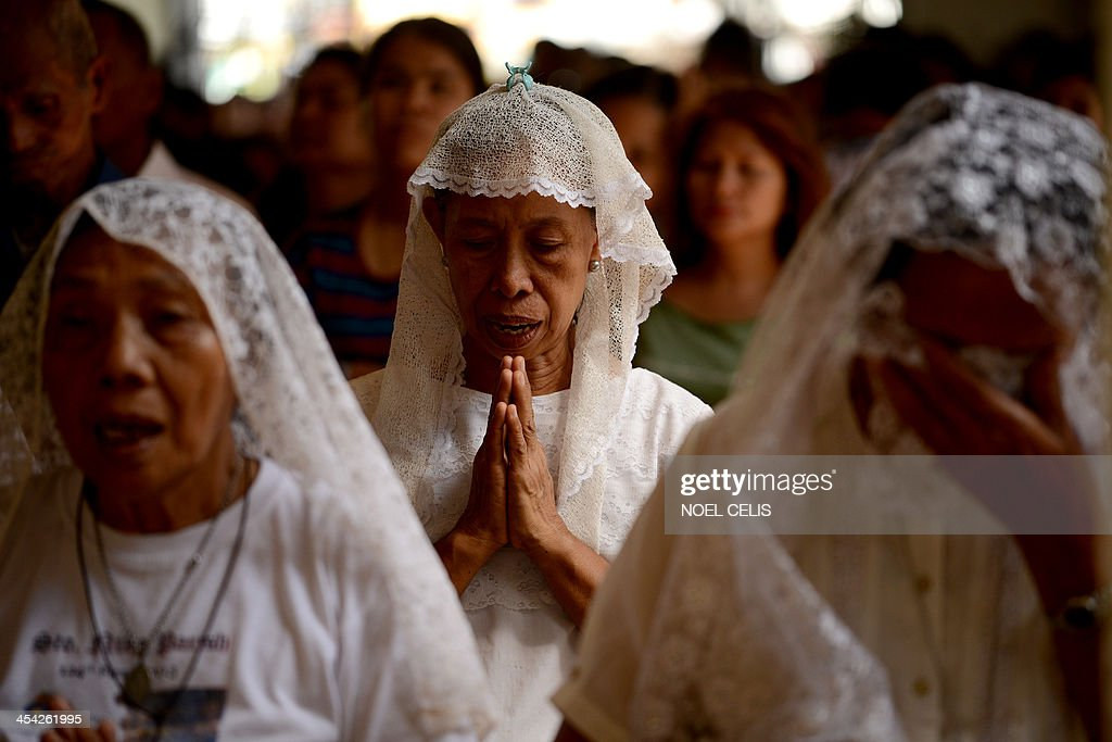 Typhoon survivors attend a morning mass at Santo Nino Church in Tacloban, eyte on December 8, 2013, commemorating one month after the typhoon. A month after one of the strongest typhoons ever recorded hit the Philippines, masses of survivors are living amid rubble in rebuilt shanty homes and experts warn rebuilding destroyed communities will take years. AFP PHOTO / Noel Celis