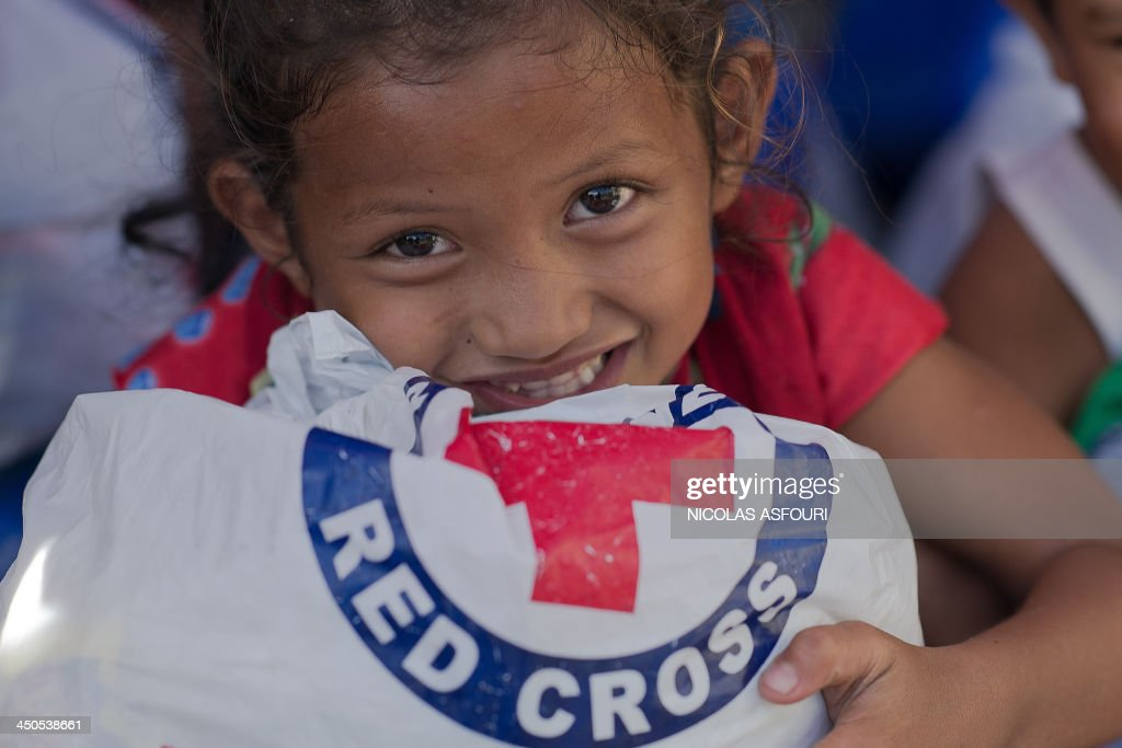 A typhoon victim holds a bag of food relief donated by the Philippines Red Cross in Tanauan on November 19 2013 The United Nations has confirmed at...