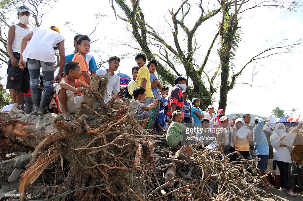 Typhoon-affected residents wait to get relief assistance on December 14, 2012 in the devastated town of New Bataan, Compostela Valley province, Philippines. More than 900 people have died and nearly a thousand remain missing after Typhoon Bopha, the strongest storm to hit the Philippines this year, pounded the region.