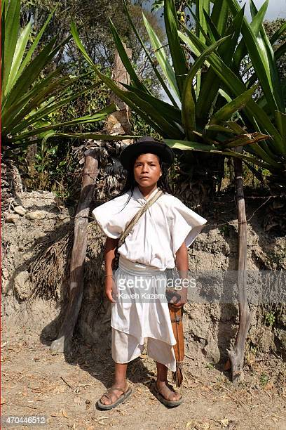 A typica Arhuaco young man stands outside his farm on January 23 2015 in Nabusimake Colombia The Arhuaco men appear in white serapes tall coned hats...