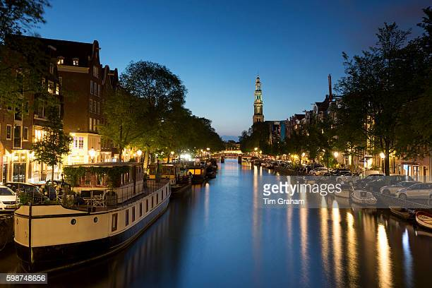 Typical Amsterdam canal scene Westerkerk church canal and barges along Prinsengracht in Amsterdam Holland