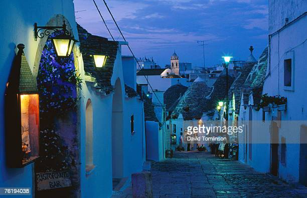 Typical cobbled lane in Trulli district at dusk, Alberobello, Puglia, Italy, Europe