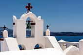 Typical Greek bell tower or steeple in the village of Fira, Greek island of Santorini, with white washed walls and blue ocean background