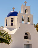View of typical Greek chapel with whitewashed walls, blue dome and bell tower in the island of Santorini, Greece