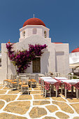 At typical Greek island chapel with white walls and red dome, and restaurant tables and chairs on the street.