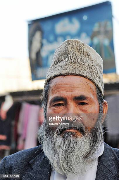 A typical Hazara Afghan male in fur hat stands outside his shop in Chicken Street on October 17 2011 in Kabul Afghanistan Chicken Street has been a...