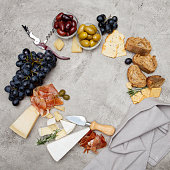 Typical italian antipasto - prosciutto, ham, cheese and olives on concrete background. Top view with copy space